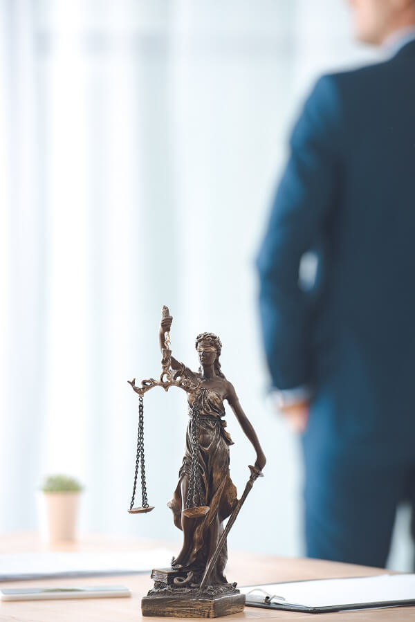 lady justice statue with a lawyer behind