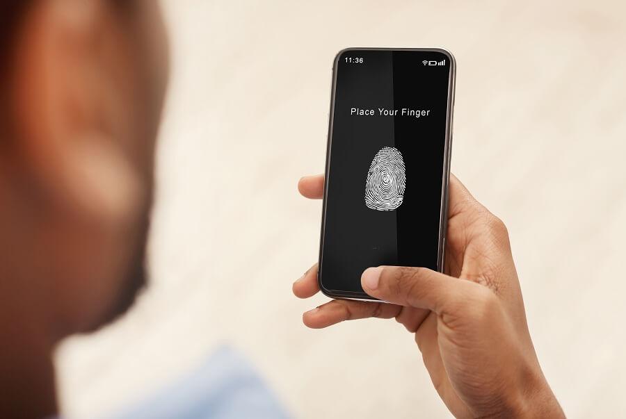 man holding phone with fingerprint scan app